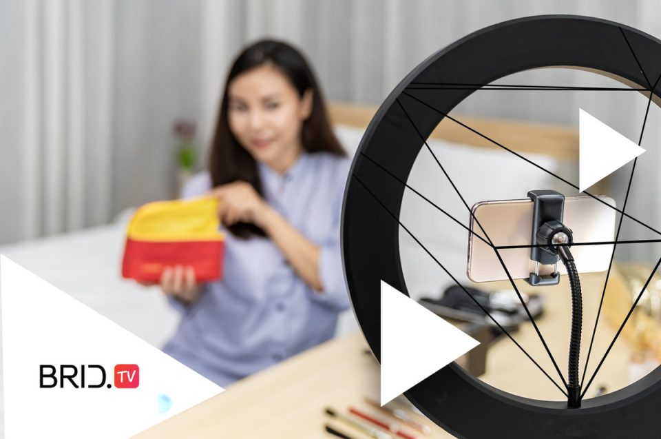 a woman sitting in front of a camera, demonstrating a product for an article on how to make a product video